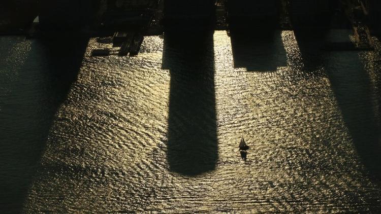 New York: Một chiếc thuyền buồm lướt qua bóng của các tòa nhà trên sông Hudson vào lúc mặt trời lặn vào ngày 20/8/2017 khi Hoa Kỳ chuẩn bị để chứng kiến nhật thực. Nhật thực xuất hiện trên khắp đất nước dọc theo một con đường từ Oregon đến South Carolina.