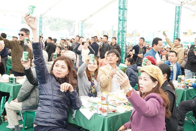 Hàng nghìn người hào hứng nâng bia uống.