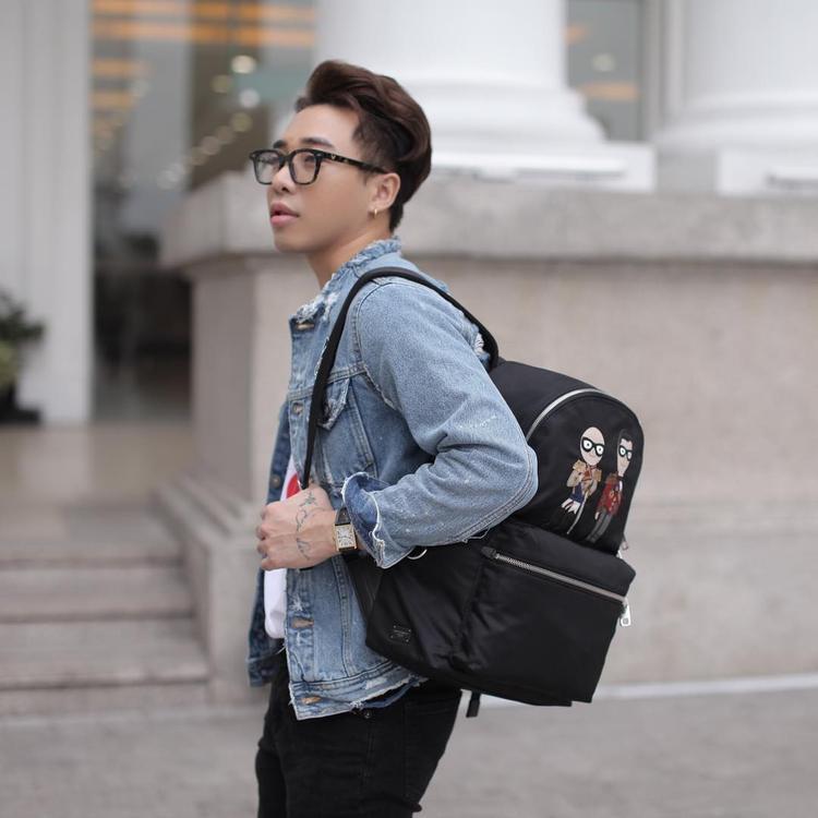 """Cả set đồ trông rất đơn giản, trẻ trung với áo khoác jeans và quần kaki, nhưng stylist Hoàng Ku lại một lần nữa giữ vững danh xưng """"stylist hàng hiệu"""" với chiếc balo đến từ nhà mốt nước Ý, Dolce & Gabbana."""