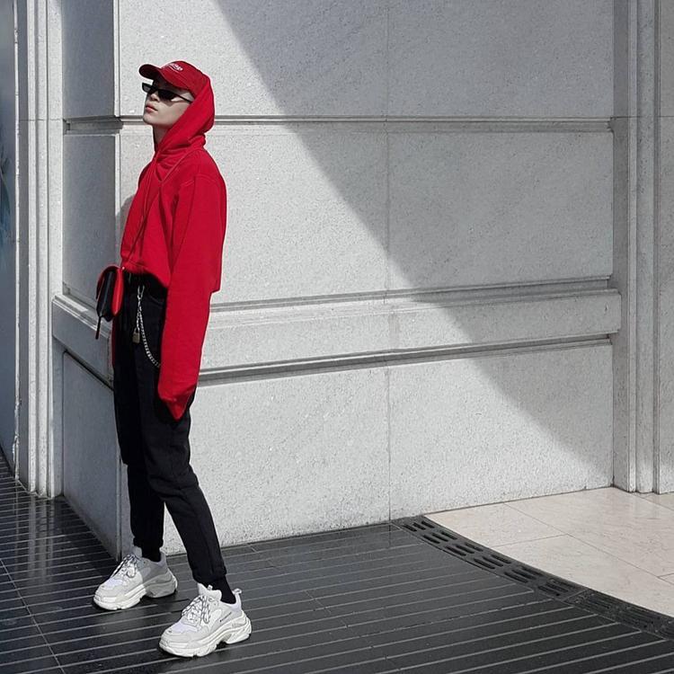 Kelbin Lei nổi bật trêh phố với chiếc hodie dáng dài tông màu đỏ đun, phối cùng jeans và đôi giày thể thao Balenciaga tông pastel.