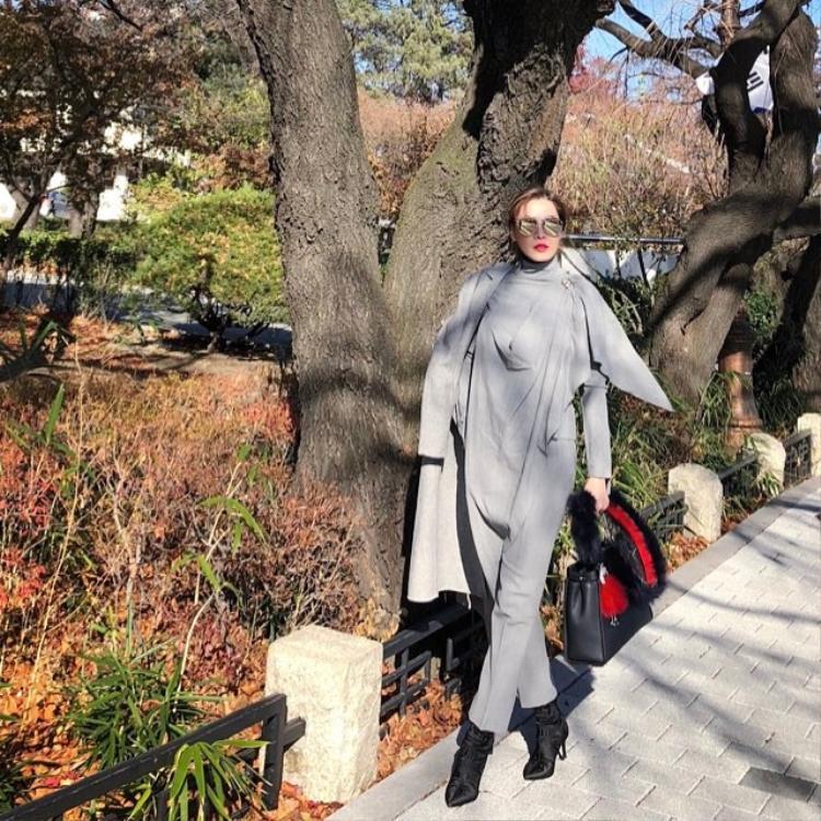 Quế Vân hút mắt người nhìn với áo khoác layer bất đối xứng phối cùng jumpsuit tông màu xám khi dạo phố Hàn Quốc. Phụ kiện boots da cùng túi to bản tăng điểm cá tính cho bà mẹ hai con.