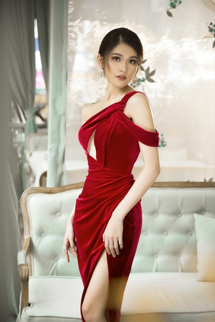 Thùy Dung trông lạ lẫm trong chiếc đầm ôm màu rượu chát. Trên nền chất liệu nhung, những đường cắt và kiểu dáng lệch vai ôm trọn vóc dáng thon thả, quyến rũ của á hậu sinh năm 1996.