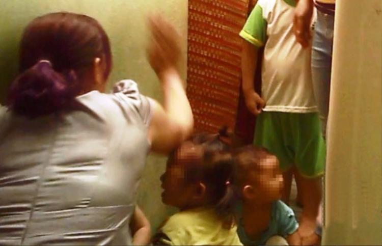 Một bảo mẫu đánh hai bé gái ở khu tắm rửa - Ảnh: Báo Tuổi trẻ