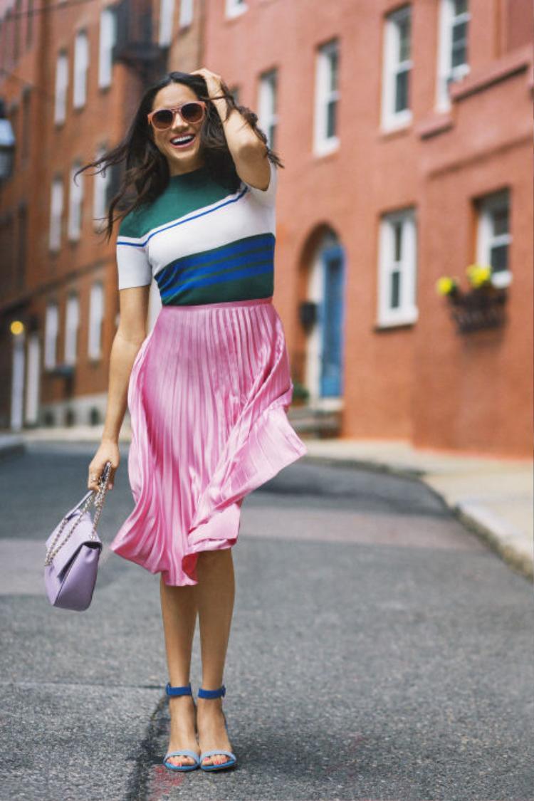 Một Meghan trẻ trung và năng động trong trang phục theo xu hướng Color Block. Từng khối màu được cô khéo léo vận dụng thật hài hòa từ cặp mắt kính cam, túi xách tím, chân váy midi xếp ly hồng, và đôi giày cao gót tiệp tông màu với kẻ sọc xanh dương của áo thun.