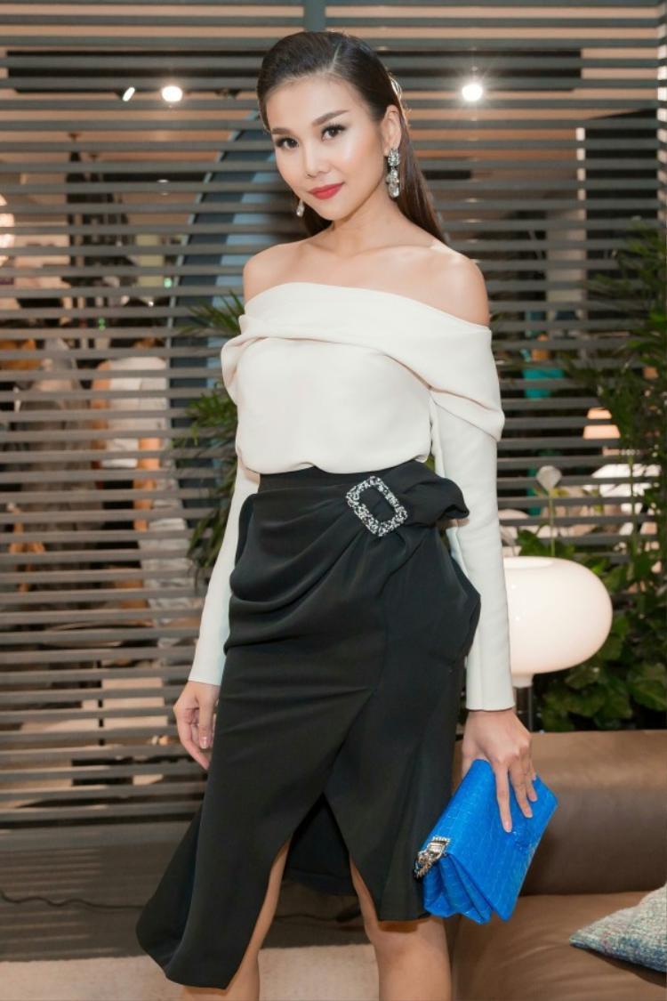 Ngay cả khi mặc set đồ đơn giản chỉ có áo trễ vai trắng và chân váy đen thì Thanh Hằng cũng có sức hút đặc biệt.