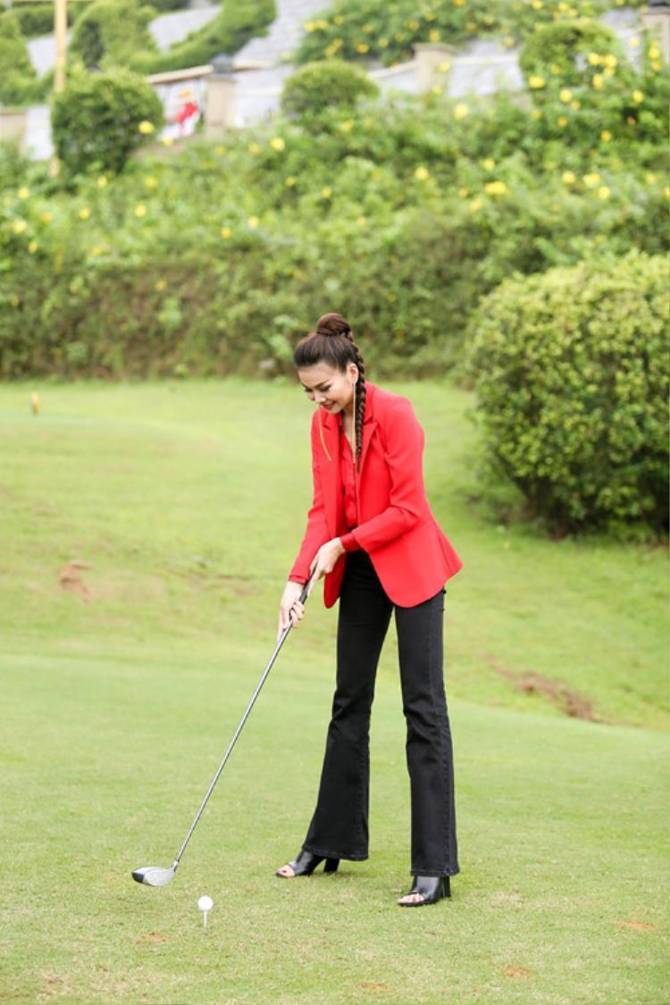 Ngay cả khi diện vest đỏ rực rỡ, Thanh Hằng cũng không hề gây phản cảm bởi cô kết hợp rất ngọt với chiếc quần ống loe khoe chân và kiểu tóc tết buộc cao trẻ trung, phù hợp với hoàn cảnh.