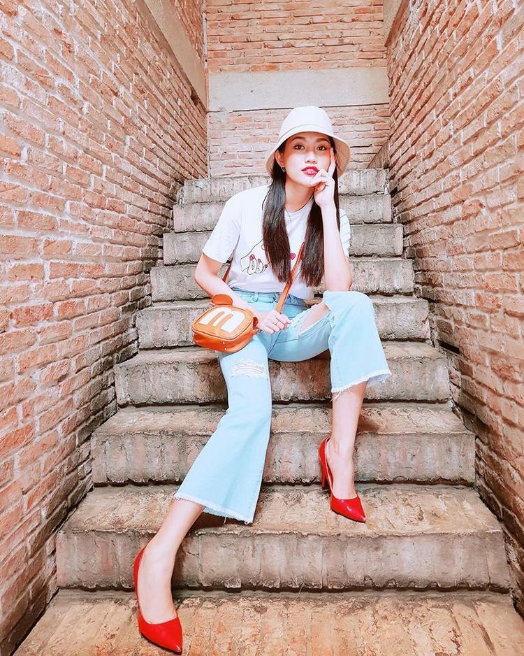 Châu diện quần ống loe và áo thun trắng basic, bù lại phụ kiện túi cam, giầy đỏ giúp outfit của cô nàng không bị chìm nghỉm.