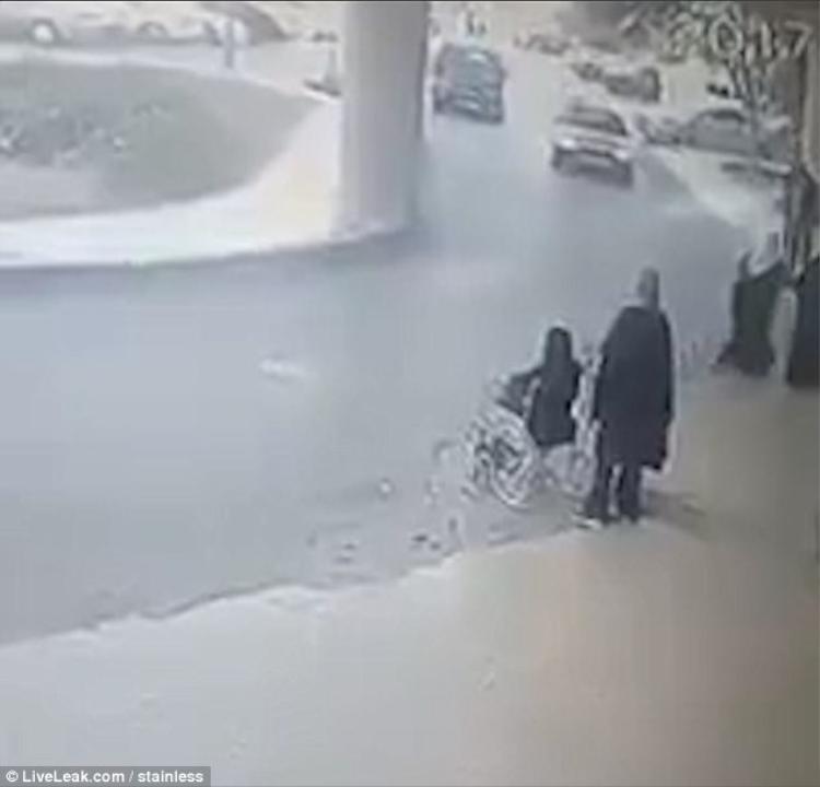 Người phụ nữ đang ngồi trên xe lăn, chờ người nhà đến đón.
