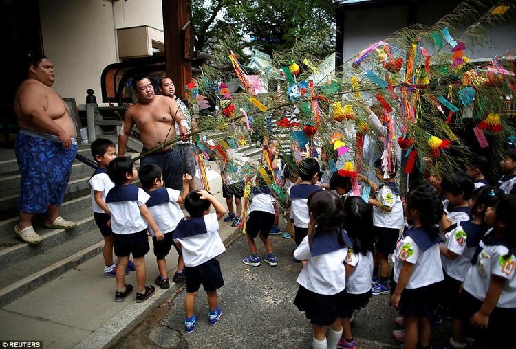 Các võ sĩ đang cùng đám trẻ nhỏ dựng cây tre được treo đầy các mảnh giấy màu, trên đó là những lời chúc của người dân dành cho họ.