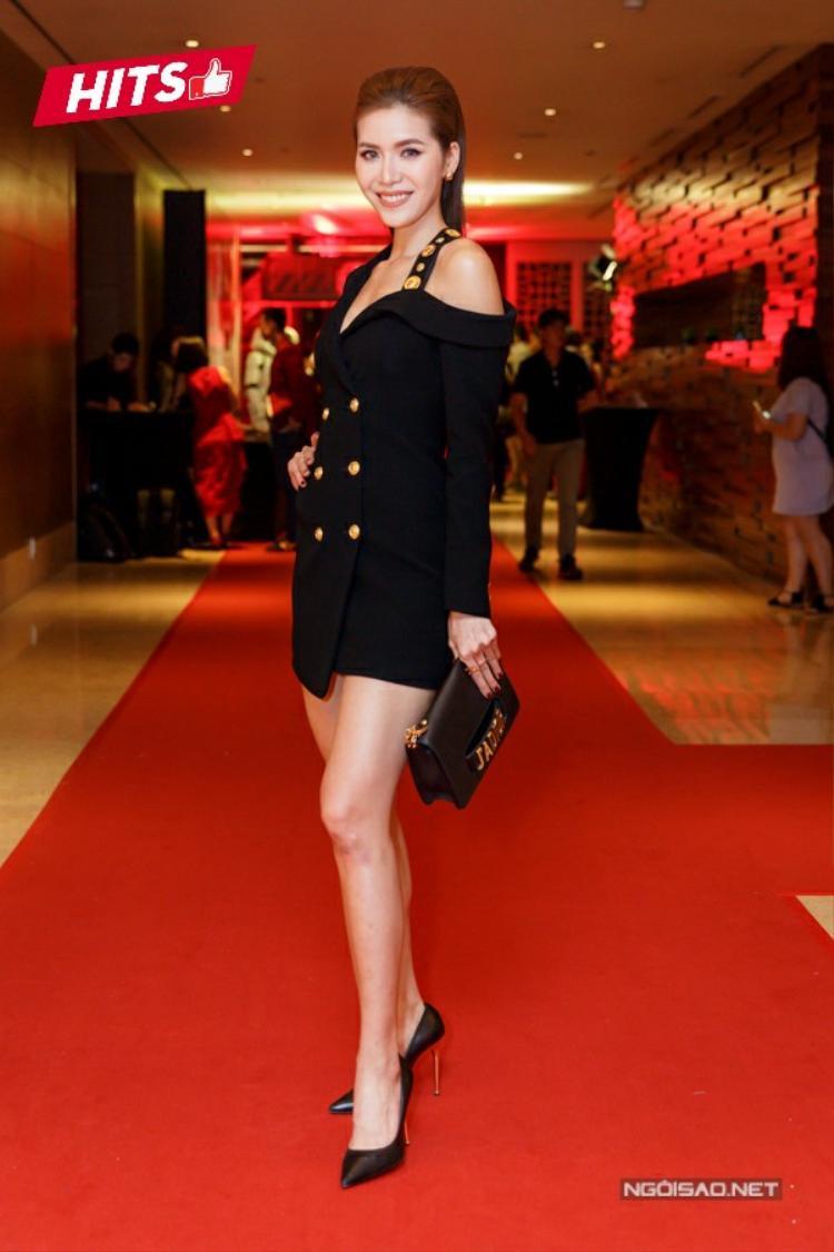 """HLV The Look, Minh Tú tiếp tục thể hiện nét gợi cảm với bộ váy vest theo xu hướng bất đối xứng thời thượng. Cách kết hợp tinh tế giữa chi tiết nút vàng đồng trên váy cùng phần khóa kéo ở túi cầm tay đem đến """"phần nhìn"""" sang trọng mà không hề """"làm quá""""."""