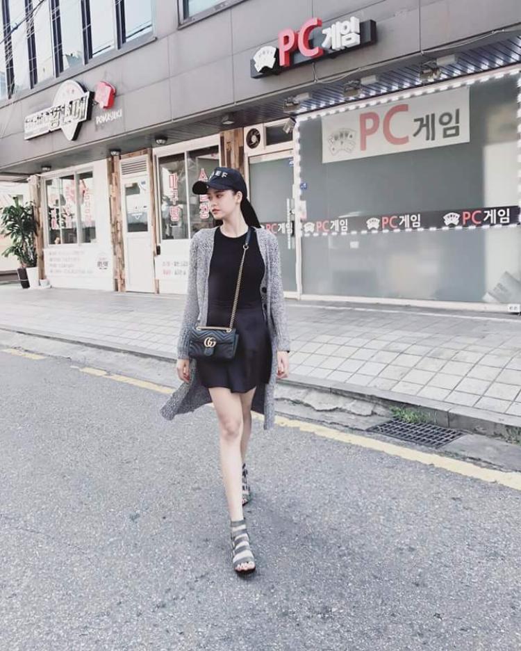 Cả cây đen được phối với áo khoác cardigan gam màu xám trung tính, nhấn nhá với chiếc túi đeo chéo thương hiệu Gucci.