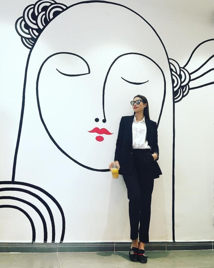 """Diện nguyên cây đen, Hoa hậu gốc Hải Phòng chọn sơ mi trắng làm điểm nhấn cho tổng thể trang phục. Mắt kính tráng gương càng làm tăng độ """"ngầu"""" của cô."""