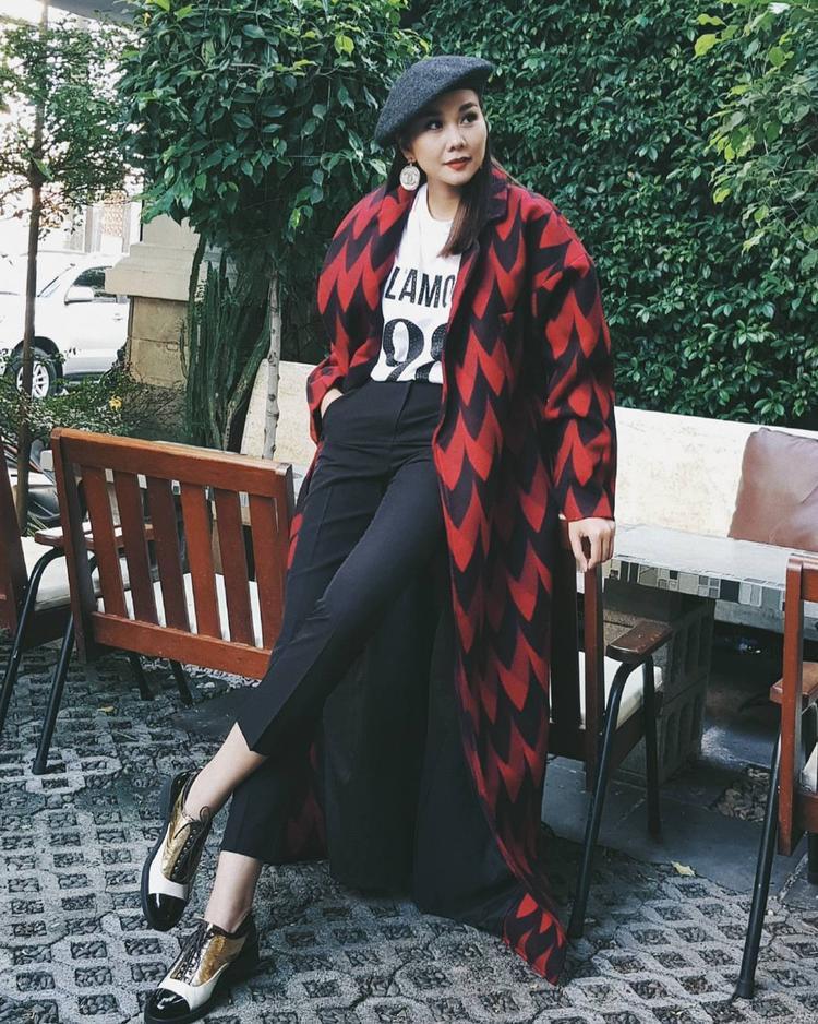 Siêu mẫu Thanh Hằng mang đến hình ảnh nam tính, mạnh mẽ với áo khoác dáng dài tông màu đỏ đen tinh tế. Cô khéo léo kết hợp set đồ đơn giản cùng mẫu giày tây ánh kim và chiếc nón beret cổ điển.