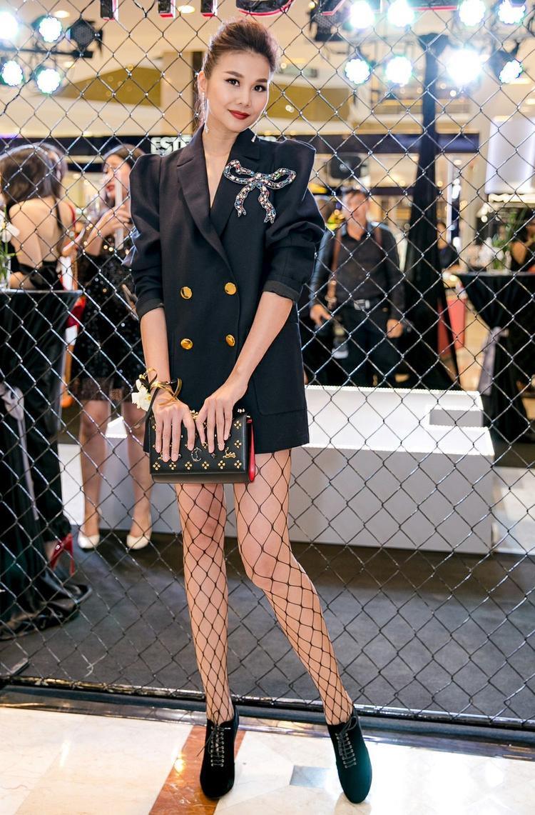 Vẫn là vest theo phong cách menswear nhưng siêu mẫu luôn biết cách tự làm mới và tạo điểm nhấn cho trang phục. Với cây đen, cô tạo điểm nhấn bằng phụ kiện nơ đính lấp lánh. Tất lưới kết hợp làm tăng vẻ địu đà nhưng vẫn rất cá tính.