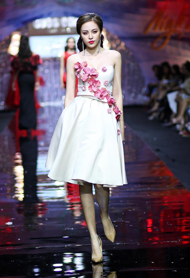 Ngoài các thiết kế tông đỏ bắt mắt, một số thiết kế có tông trắng nền nã, kết hoa sinh động ở thân trước. Trong ảnh, Mina Lê trình diễn mẫu váy nhẹ nhàng, hoạ tiết hoa lan 3D nổi bật trên thân trước.