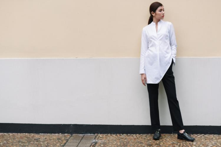 Vẫn là sơ mi và quần âu, nhưng set đồ này cá tính hơn với cặp đôi đen - trắng kinh điển. Chiếc áo sơ mi trắng vạt chéo ấn tượng và khác biệt hơn với chi tiết vạt bất đối xứng.Phần cổ V sâu tôn trọn vóc dáng thanh mảnh của vóc dáng thon gọn chưa đầy 50kg của cô.
