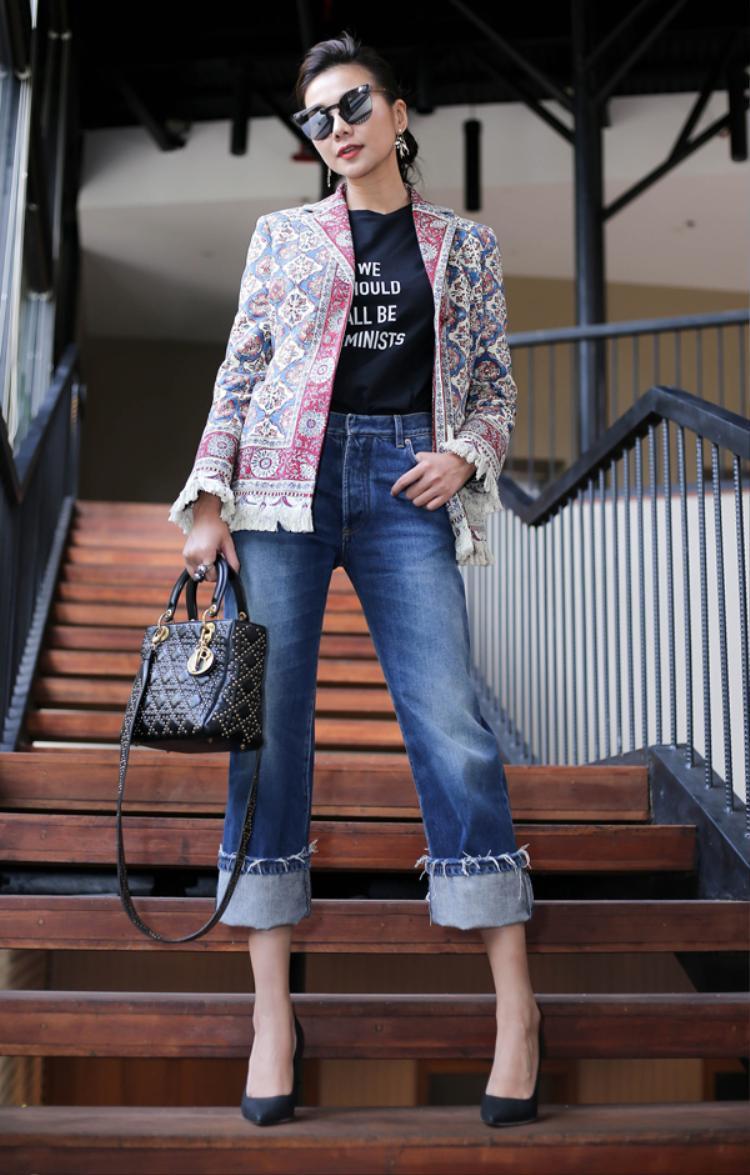 Thanh Hằng diện áo thun cùng quần jean ống rộng khá đơn giản. Siêu mẫu kết hợp phụ kiện ăn ý với trang phục. Mắt kính đen, túi xách, giày cao gót thương hiệu Christian Dior. Đặc biệt nhất, cô kết hợp áo vest thổ cẩm khoác ngoài tạo sự lạ mắt nhưng vẫn vô cùng thời trang.