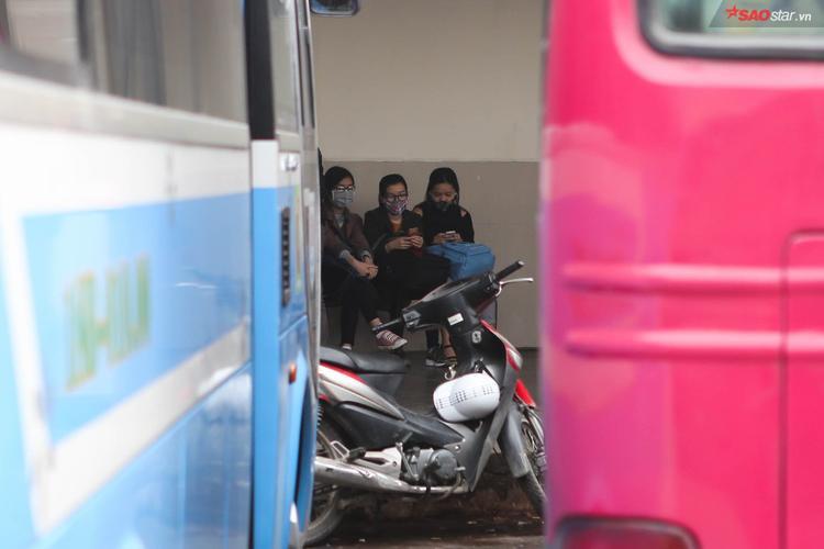 Nhóm sinh viên ngồi chờ xe chuyển bánh.