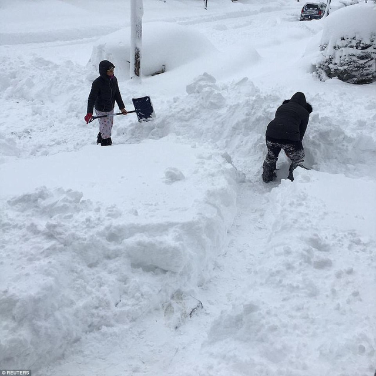 Người dân Mỹ ở Erie, Pennsylvania cào các lớp tuyết dày gần 1 m để có thể lưu thông. (Ảnh: Reuters)