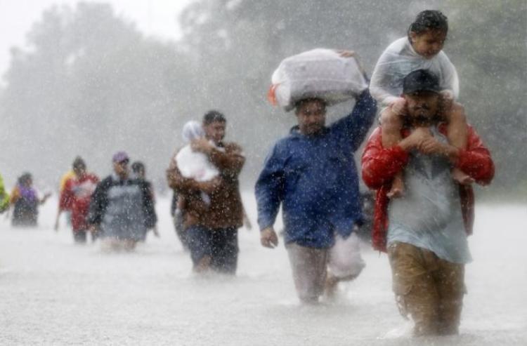 """Người dân lội qua vùng nước lũ trong """"cơn bão thập kỷ"""" Harvey tại Houston, Texas (Mỹ) ngày 28/8. Cơn bão đã cướp đi sinh mạng của 60 người, khiến 1 triệu người phải rời nhà cửa, phá hủy khoảng 200.000 ngôi nhà. Đây được xem là cơn bão tồi tệ nhất tấn công bang Texas trong vòng 50 năm đã gây thiệt hại lên tới 180 tỷ USD, cao hơn cả thảm họa do bão Katrina gây ra năm 2005 (120 tỷ USD."""