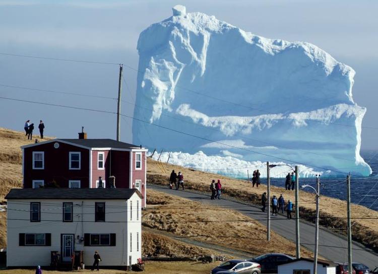 """Nhiều du khách đổ về thị trấn Ferryland (Canada) để ngắm tảng băng trôi bất ngờ dừng lại ven Bờ biển phía Nam ngày 16/4. Ứớc tính chiều ngang của tảng băng có thể lên tới hơn 200 m, cao khoảng 45 - 73 m. Ferryland còn có tên là """"Iceberg Alley"""" vì những tảng băng trôi từ Bắc Cực sẽ dạt qua vùng bờ biển của tỉnh Newfoundland và Labrador từ mùa xuân cho tới tháng 9 hàng năm. Theo các chuyên gia, hiện tượng băng trôi là do gió lớn và sự nóng lên toàn cầu."""