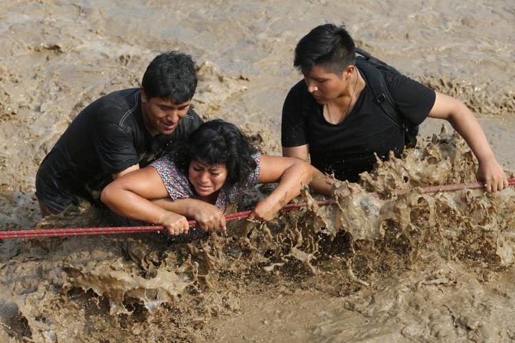 Người dân bám chặt dây để di chuyển qua con đường bịn ngập sau trận lở đất lũ lụt ở quận Huachipa, Lima, Peru, ngày 17/3.