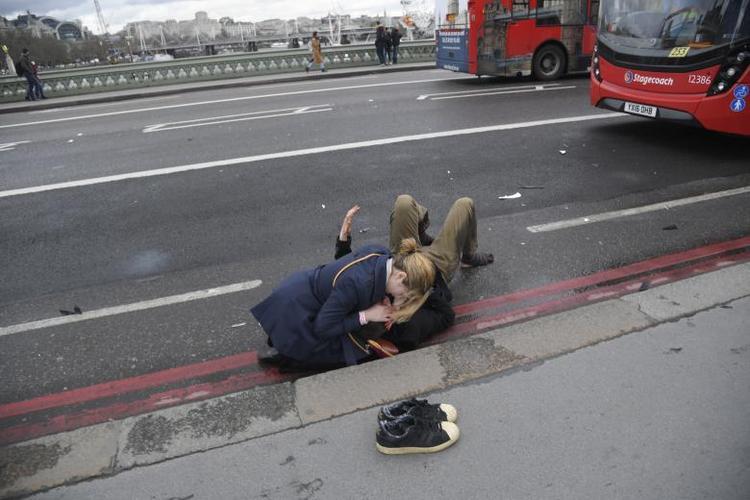 Một người phụ nữ đang cố gắng cứu giúp người đàn ông bị thương trong vụ lao xe và đâm dao khủng bố trên cầu Westminster, London (Anh) ngày 22/3, khiến 5 người thiệt mạng.