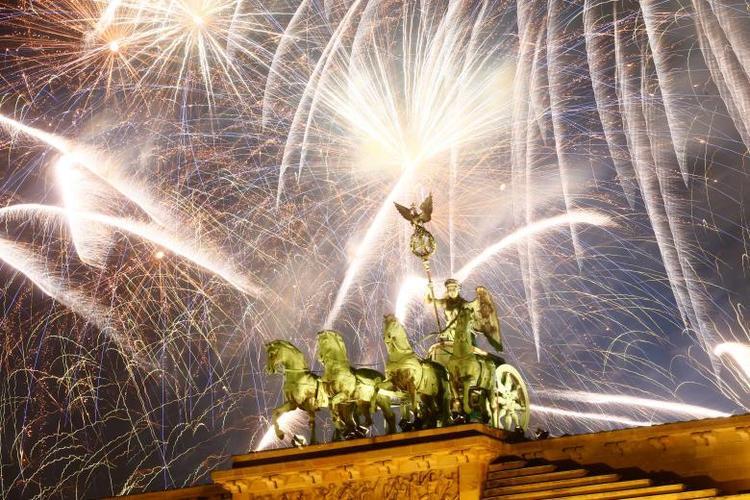 """Vào lúc 6h (giờ Hà Nội), năm 2018 """"gõ cửa"""" nước Đức. Tượng đài Quadriga cổng Brandenburg ở thủ đô Berlin của Đức được chiếu sáng bởi màn pháo hóa muôn màu trong đêm giao thừa."""