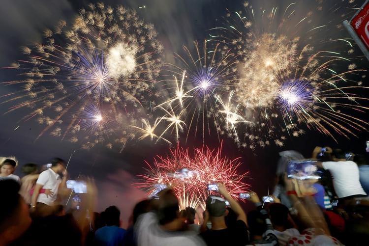 Người dân ghi lại màn trình diễn pháo hoa tại thành phố Pasay phía nam Manila, Philippines.