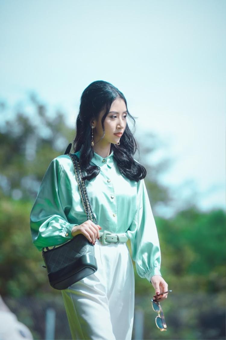 Hóa thân thành cô nàng vintage nữ tính với sơ mi tay bồng kết hợp quần ống suông chất liệu lụa bóng, túi xách tiệp màu.