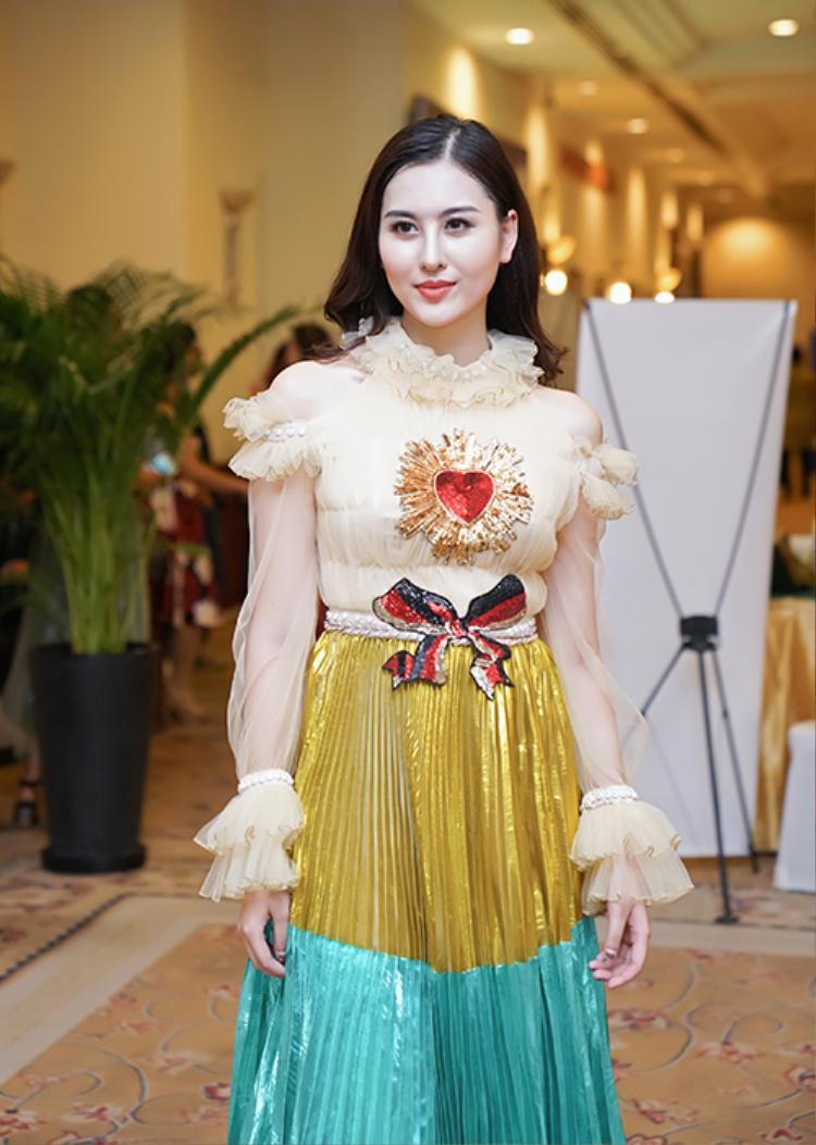 Đây là lần đầu tiên người đẹp xuất hiện trước công chúng sau khi trở thành Á hoàng 1 Nữ hoàng Trang sức Việt Nam. Chiếc váy chia thành nhiều tầng màu sắc, thân trên là vải xuyên thấu đắp bèo nhún rất cầu kỳ.