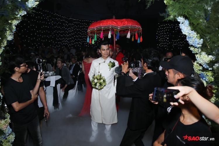 Chú rể Phi Hùng diện áo dài trắng, bước vào sảnh tiệc.
