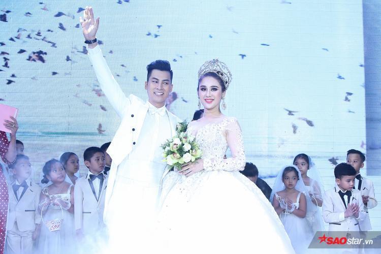 Hai vợ chồng tươi cười, vẫy tay chào toàn thể khách mời.