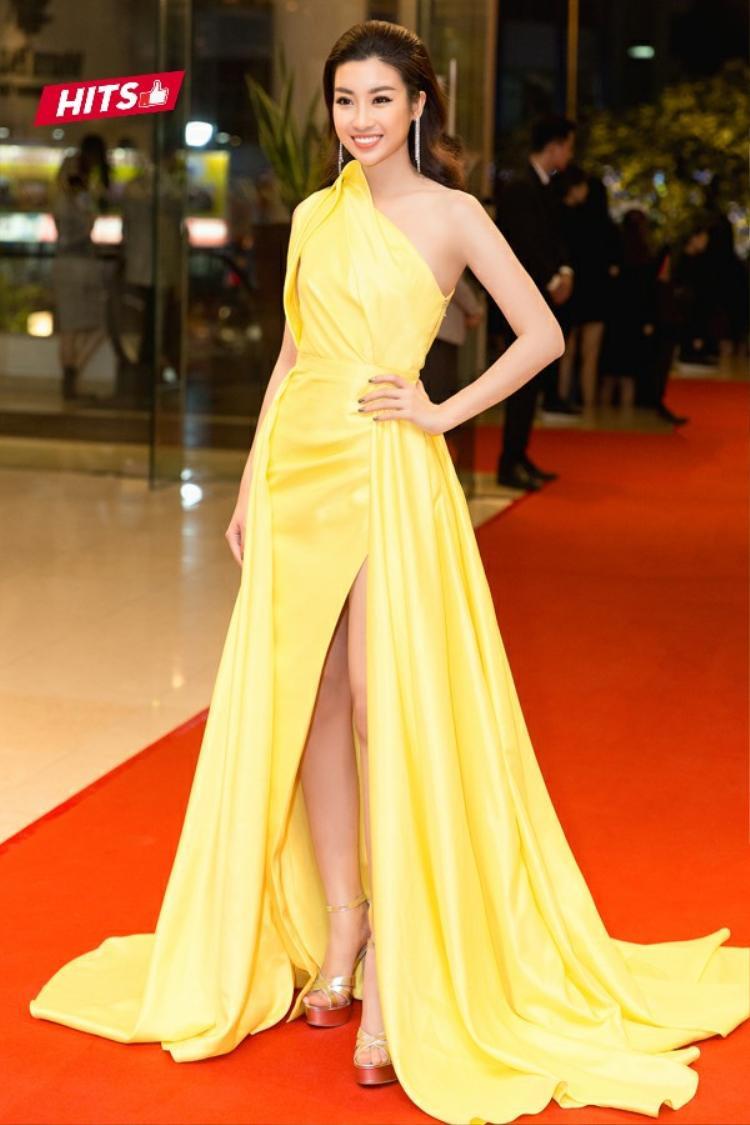 Đỗ Mỹ Linh cũng đem đến nét tươi tắn, trẻ trung khi lựa chọn bộ váy lệch vai gam màu vàng nổi bật. Chi tiết xẻ cao giúp người đẹp khoe đôi chân thon dài. Đồng thời, cách kết hợp phụ kiện hoa tai dáng dài và giày cùng tông cũng được cho là hoàn toàn phù hợp với tổng thể.