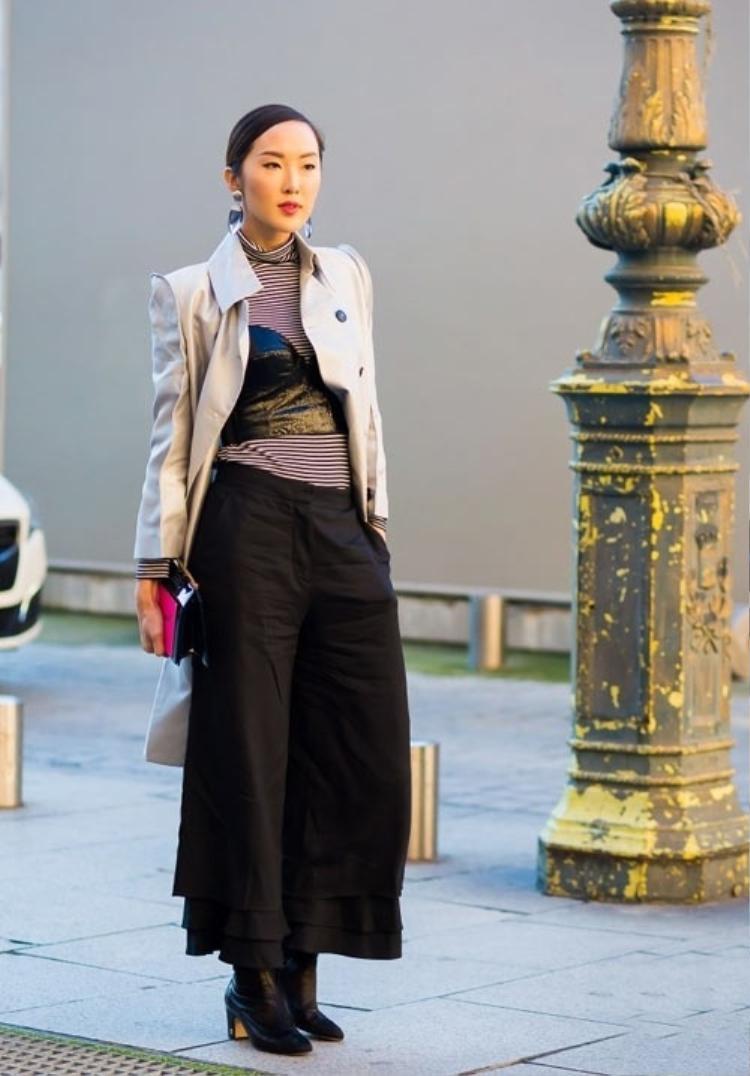 Fashionista Chriselle Lim sử dụng nội y da để mặc ngoài áo thun cao cổ, kết hợp với quần ống suông có phần gấu xếp bèo lạ mắt.