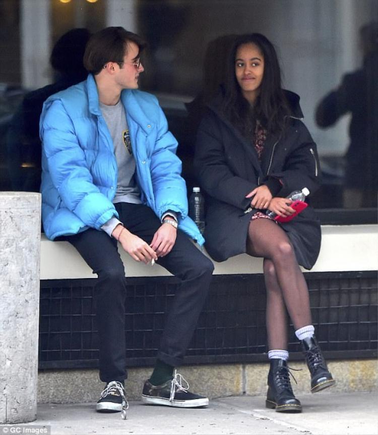 Malia Obama diện váy xòe hoa, áo khoác đen cùng đôi boot đen trẻ trung. Trong khi đó, bạn trai Rory mặc một chiếc áo khoác xanh da trời, đeo kính râm.