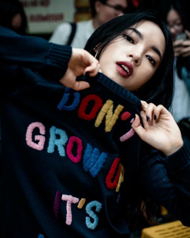 """Châu Bùi cá tính với với chiếc áo len và màu nail đen cá tính. Điểm nổi bật của item này chính là dòng chữ """"Don't grow up Its a trap"""" đầy màu sắc."""