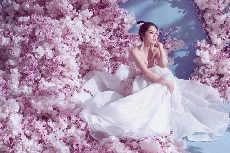 Giữa bối cảnh ngập tràn hoa đào, Dương Cẩm Lynh diện những thiết kế cúp ngực với tông màu pastel ngọt ngào, khoe trọn khuôn ngực đầy và bờ vai mảnh khảnh, trắng ngần.