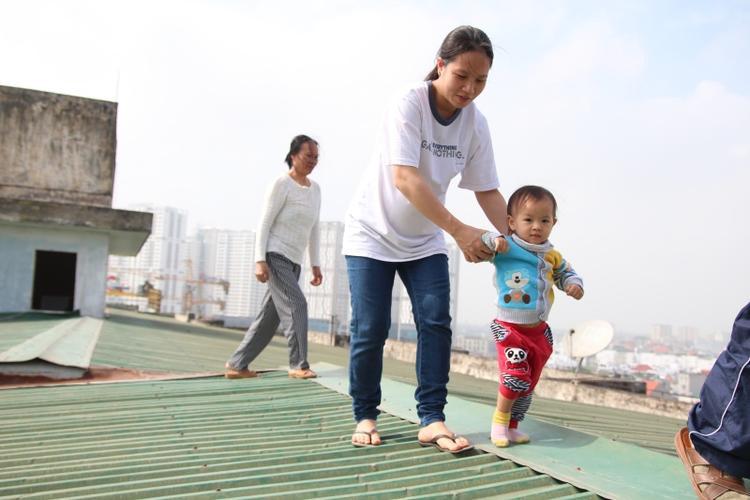 Chị Lan đang mang thai ở tháng thứ 8 dắt con nhỏ đi qua mái nhà từ đơn nguyên 3 sang thang máy ở đơn nguyên 2 đi nhờ.