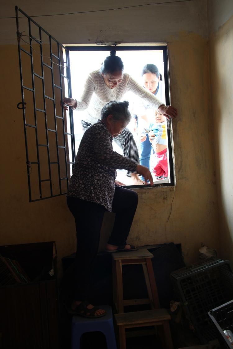Người dân phải chui qua cửa tầng tum để đi qua mái nhà.