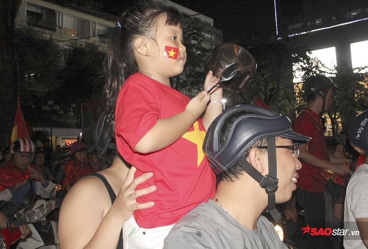Một bé gái xinh xắn để lại ấn tượng mạnh khi cổ vũ không khí bằng thìa ăn cơm và nồi.