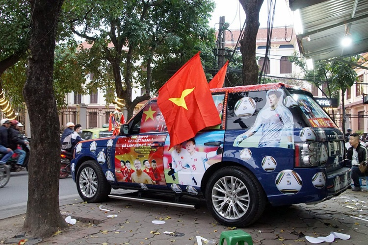 Vừa dán kín xe, chủ ô tô còn treo 2 lá Quốc kỳ khá lớn.