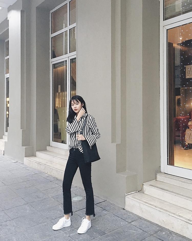 Chỉ với 2 tông màu đen, trắng Phí Phương Anh đã có ngay 1 set đồ hợp mốt. Cách phối áo sơ mi sọc đóng thùng nửa vời cùng quần kaki đem đến cho cô nàng vẻ năng động, cá tính.