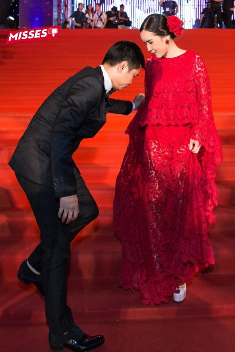 Thậm chí, để bước lên bục thảm đỏ, phần váy dài quá vướng víu khiến Lưu Hương Giang còn phải cậy nhờ phu quân của mình - nhạc sĩ Hồ Hoài Anh giúp sức. Ngoài ra, bông hoa đỏ cài tóc cũng phần nào khiến cô trở nên sến sẩm.