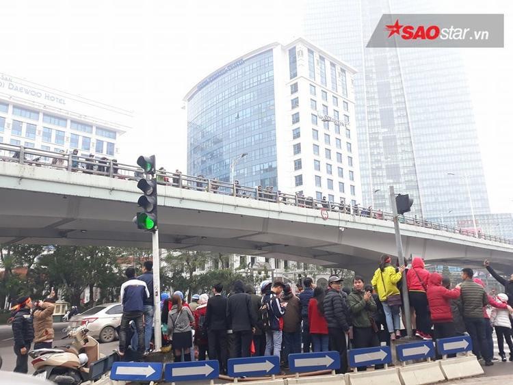 Cầu vượt Nguyễn Chí Thanh và khu vực cột đèn đường chật kín người đứng chờ.