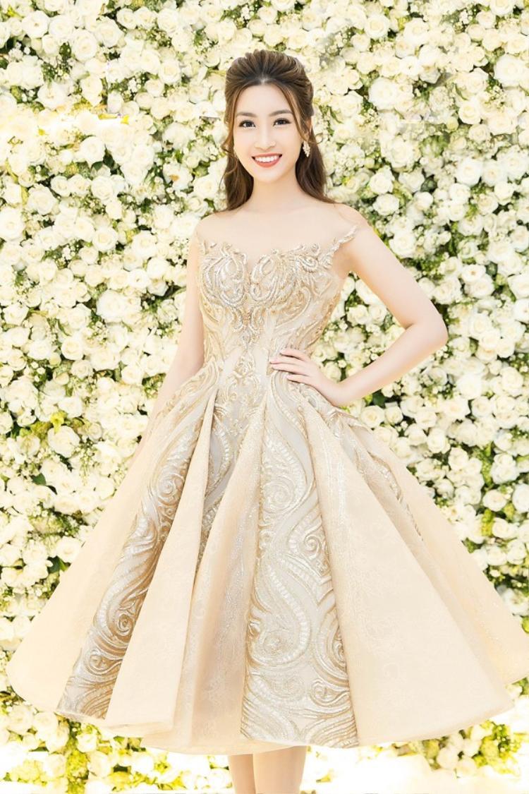 Tham dự sự kiện ra mắt cơ sở làm đẹp vào tháng 8/2017 tại TP.HCM, Hoa hậu Đỗ Mỹ Linh lộng lẫy trong thiết kế đầm xòe bồng màu đồng ánh kim vô cùng sang trọng. Kiểu tóc đơn giản nhưng vô cùng tinh tế góp phần tăng sự sang trọng cho người mặc.