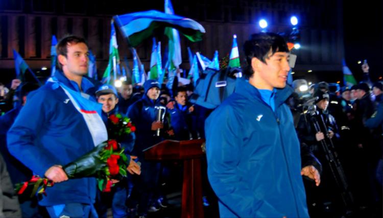 Những cầu thủ của đội tuyển U23 Uzbekistan mặc áo khoác xanh, khoác cờ trên người và tay cầm những bó hoa tươi thắm từ người hâm mộ và chính phủ nước này trao tặng.