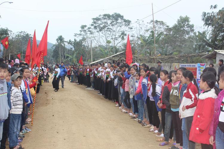 Nhiều học sinh và người dân chào đón hai bên đường.