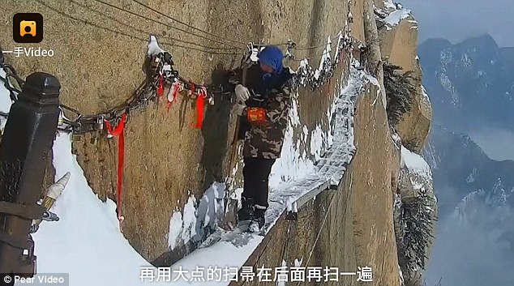 Trên vách núi cao hơn 2.000m, các công nhân phải dọn tuyết trên đó với đồ bảo hộ đơn giản.