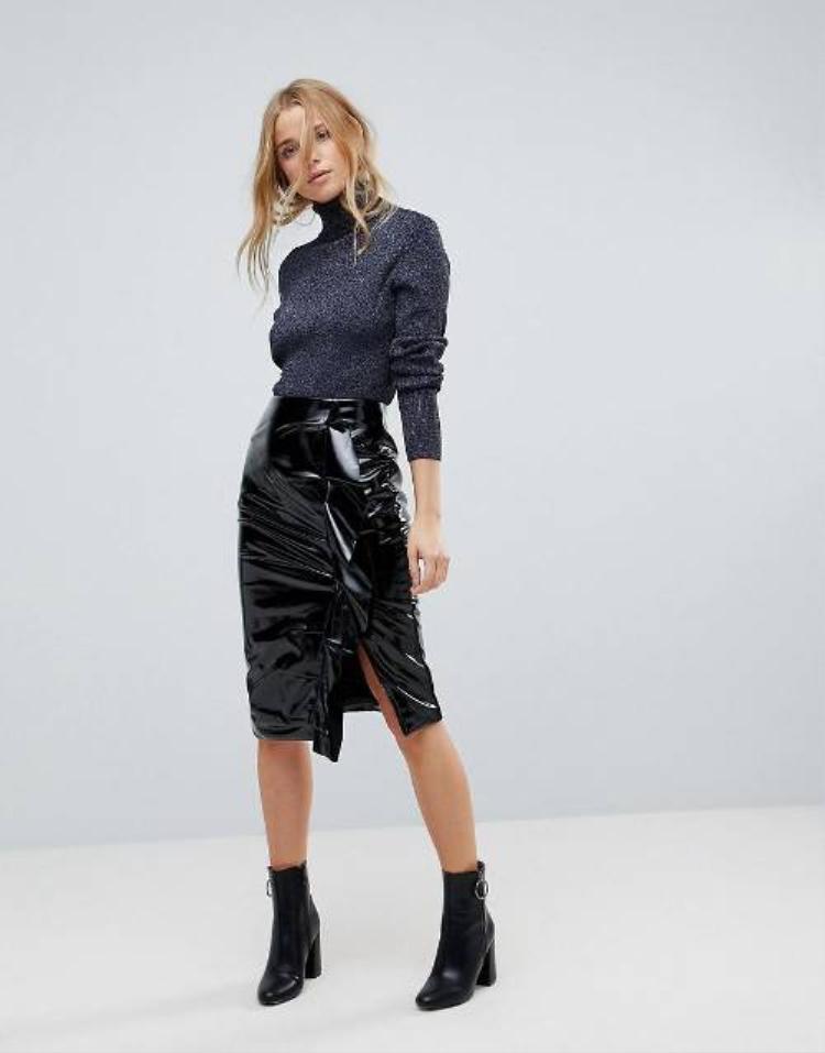 Quí cô hiện đại được khoác lên mình chiếc váy xà-rông da bóng kết hợp với áo len cổ lọ twinkle. Một đôi bốt đen là sự kết hợp tuyệt vời với váy da cá tính.